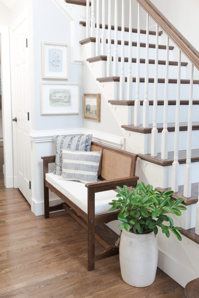 Home entryway bench from Facebook Marketplace next to staircase with pictures on the walls, pillows on the bench and a green potted plant.
