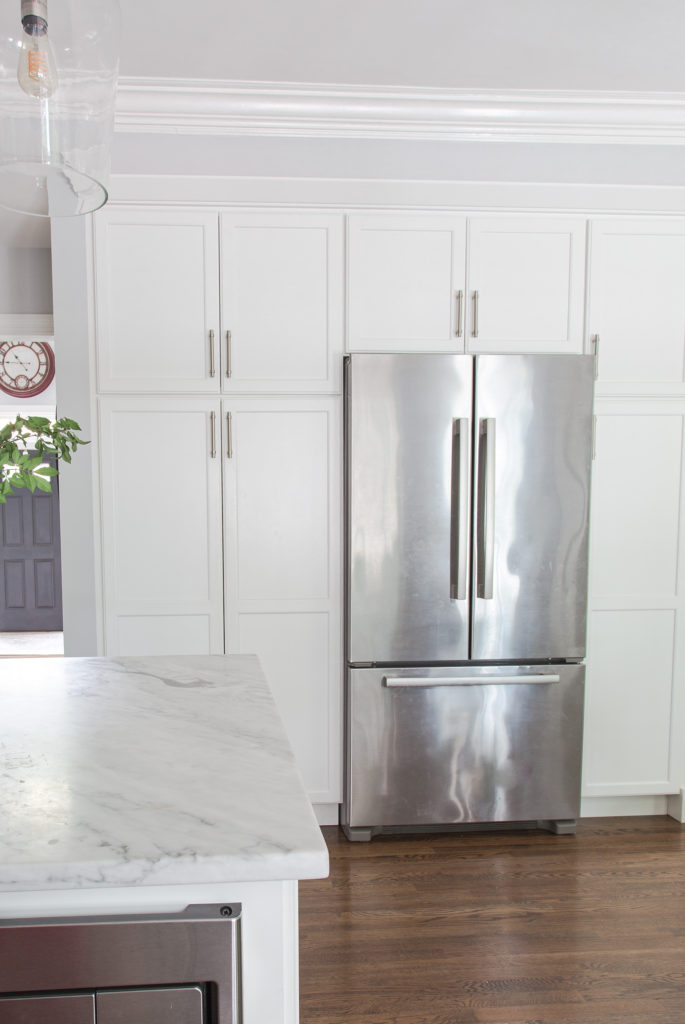 white kitchen pantry cabinets with stainless steel fridge