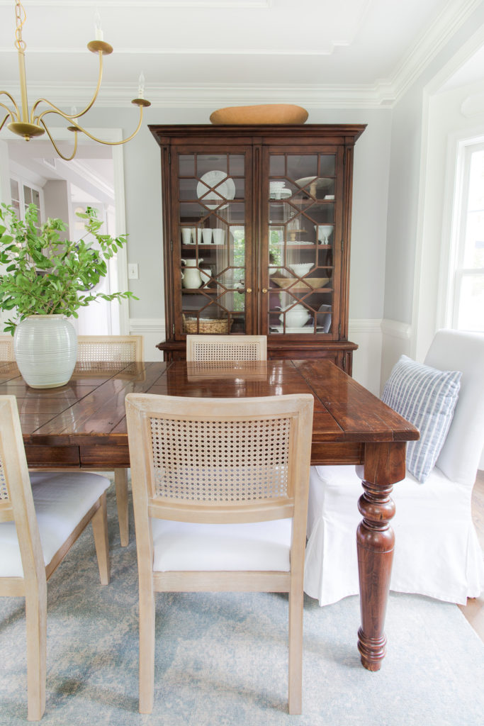 Dining room with china cabinet from Facebook Marketplace, table, cane chairs and a urn of fresh green branches