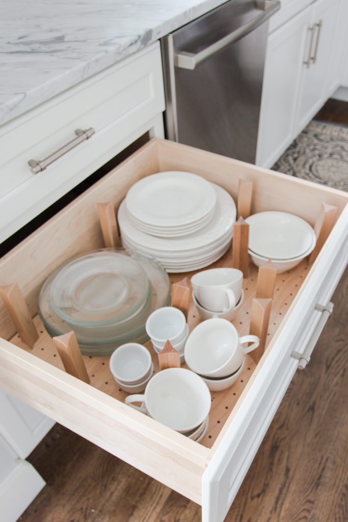 Organize kitchen cabinets with white plates and cups