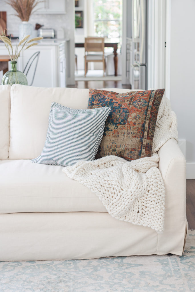 Slipcovered sofa with blanket and pillows