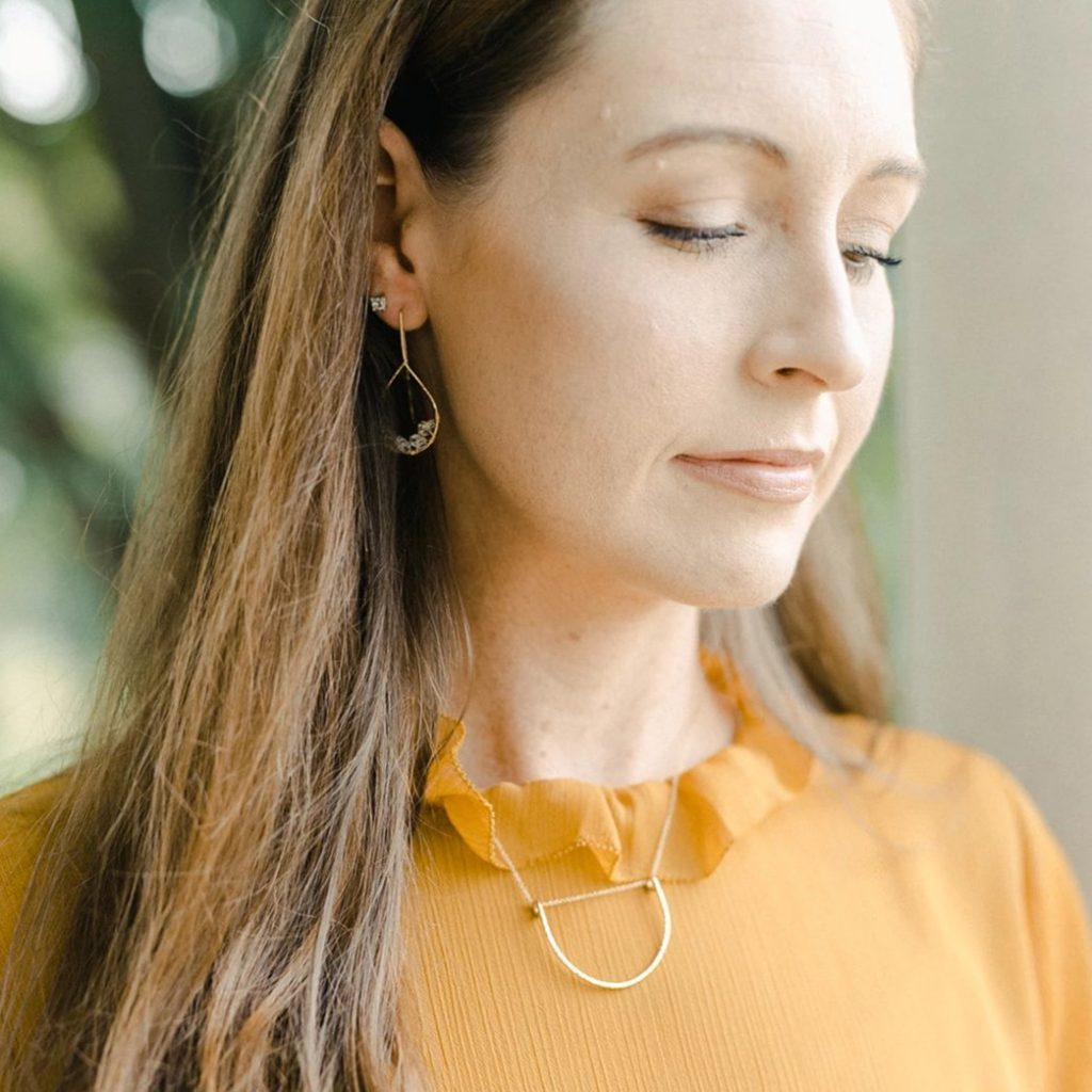 model wearing gold textured necklace