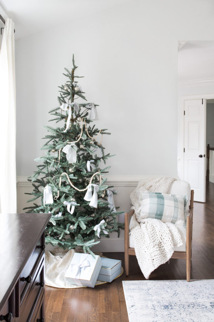 Christmas tree in bedroom with chair next to tree and presents underneath