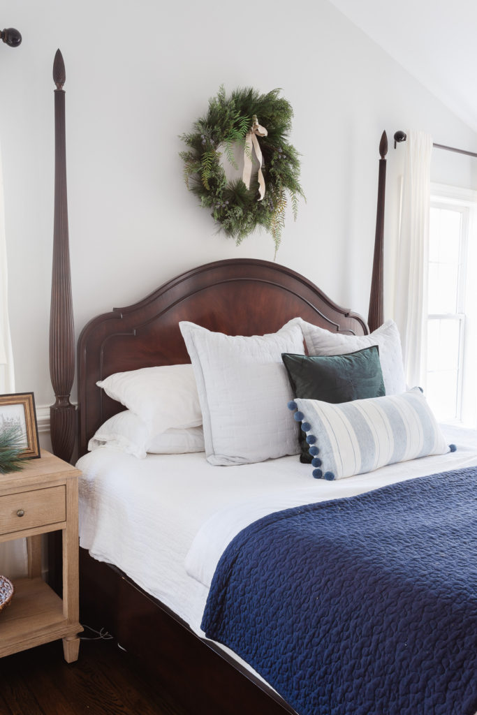 Poster bed with blue quilt and wreath on wall in bedroom