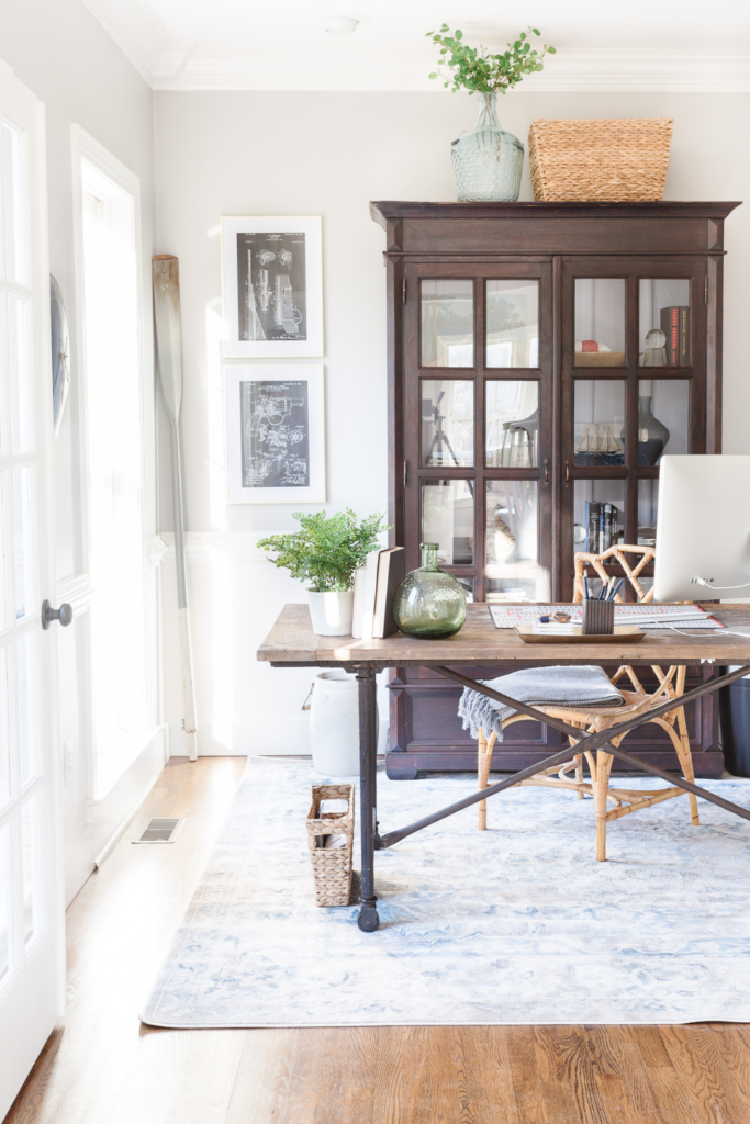 Home office desk and bookcase with rug and art on the walls