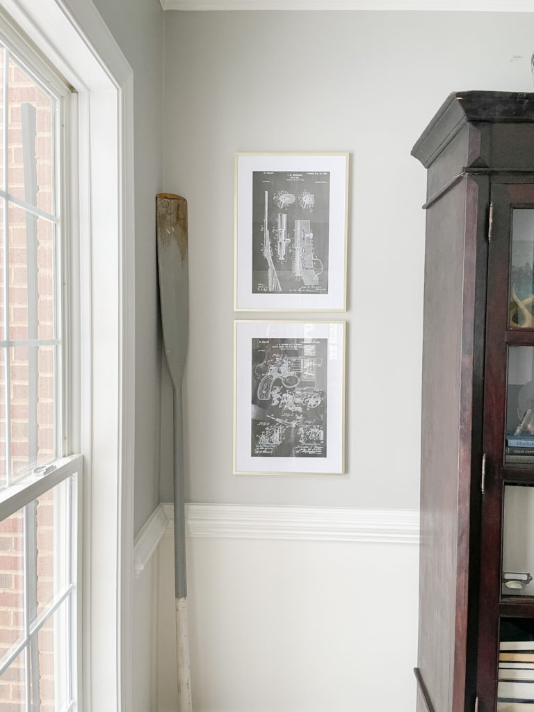 Two blue print sketches in gold frames hanging on the wall
